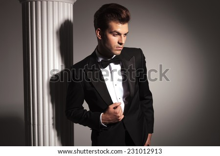 Handsome young elegant business man fixing his jacket while looking down.