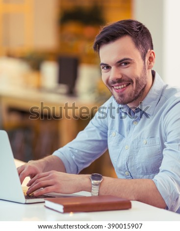 Handsome young freelancer is using a laptop, looking at camera and smiling while working at the coffee shop