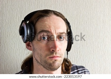 Handsome young long hair man with headphones looking at camera