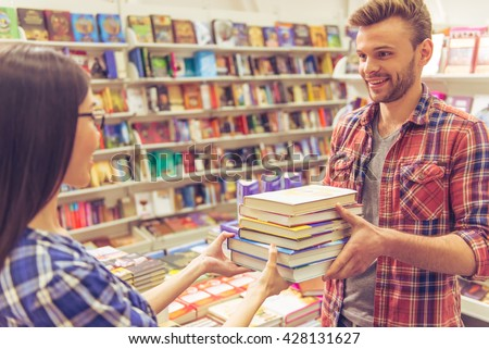 Handsome young man and nice woman are holding a pile of books, looking at each other and smiling while standing in the book shop