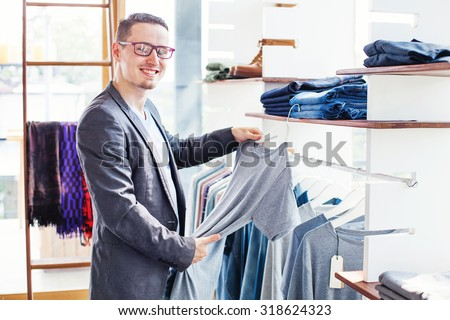 handsome young man choosing clothes in a shop