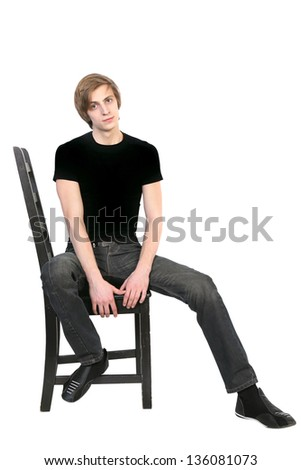 Handsome young  man in black clothes  sitting on a chair on white background