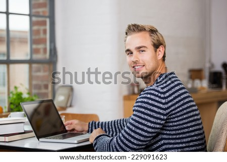 Handsome young man in casual clothes working from home on his laptop computer turning to smile at the camera