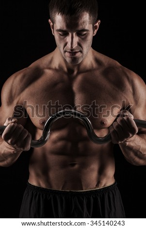 handsome young man on wall background doing exercises for the biceps