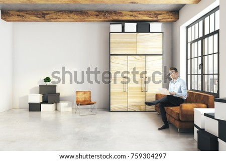 Handsome Young Man Using Laptop In Modern Living Room Interior With  Furniture And Empty Wall.