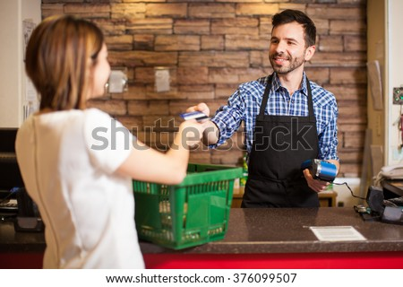 Handsome young man with a beard taking a credit card from a customer at a grocery store