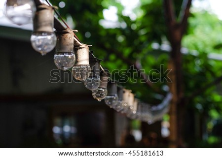 Hanging decorative lights for a wedding party in the garden after the rain and cobweb. Low light photo
