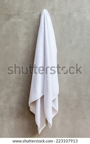 Hanging white and clean towel draped on exposed concrete wall in the bathroom.
