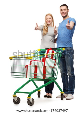 happiness, holidays, shopping and couple concept - smiling couple with shopping cart and gift boxes in it showing thumbs up