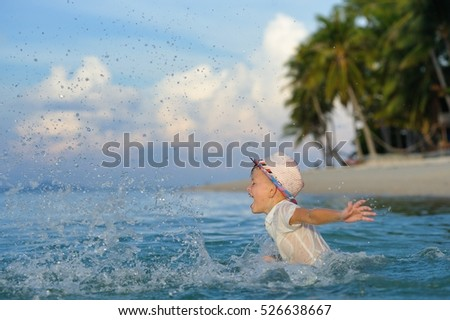 Happiness portrait in tropical water: gallant, handsome 8 years old boy in wet shadeless bright slim fit shirt and fedora hat sitting in the sea water, happily making splashes, half-face