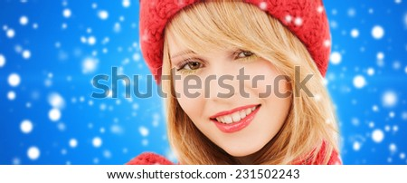 happiness, winter holidays, christmas and people concept - close up of smiling young woman in red hat and scarf over blue snowy background