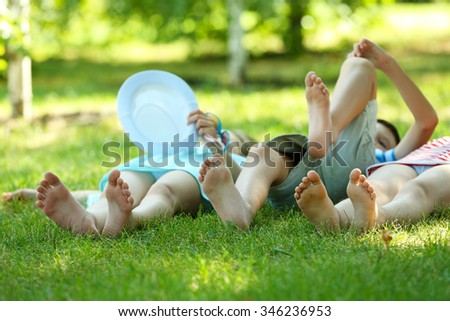 Happy active children lying on green grass in park