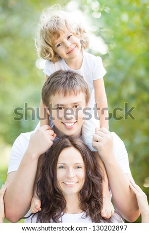 Happy active family having fun outdoors in spring park against natural green background