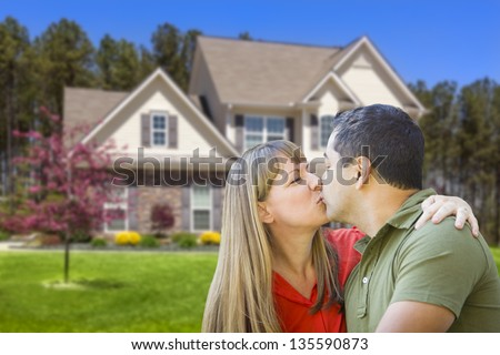 Happy Affectionate Mixed Race Couple Hugging in Front of House.