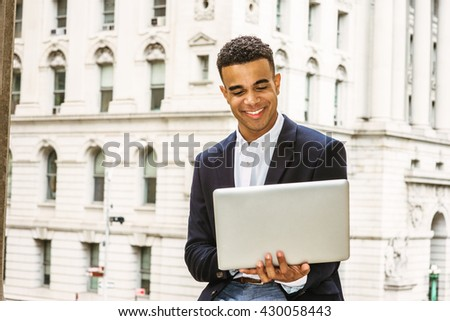 Happy African American college student studying in New York, wearing black blazer, sitting by vintage office building on campus, reading, working on laptop computer, smiling. Instagram filtered effect