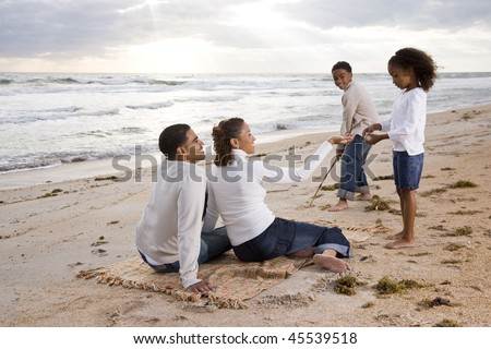 Happy African-American family of four standing on beach with beautiful sunlight