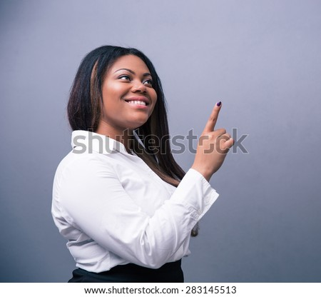 Happy african businesswoman pointing finger up over gray background