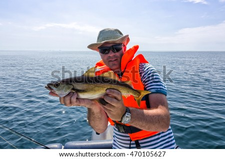 Happy angler with pollack fish