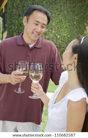 Happy Asian couple holding glasses of wine