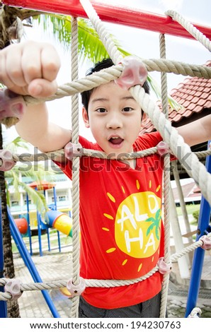 Happy asian cute boy playing on playground .