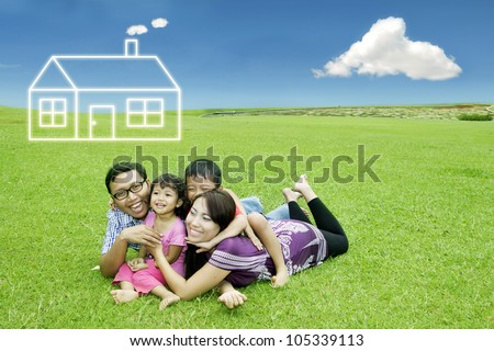 Happy asian family lying on the meadow with dream house