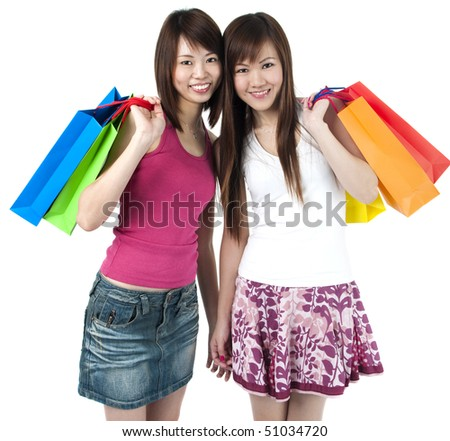 Happy Asian girls standing with shopping bags against white background.