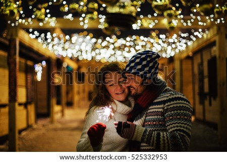 Happy attractive couple in a christmas market at night. Beautiful bokeh lights background.