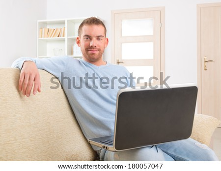 Happy attractive handsome man sitting on the sofa and using laptop