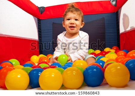 Happy baby boy having fun with colorful balls inside playpen