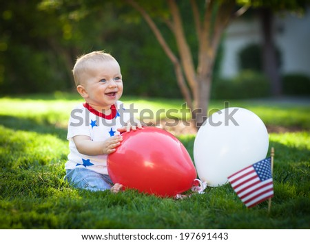 Happy baby boy playing with rend and white ballons on a green lawn