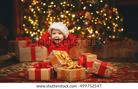 Happy baby by a Christmas tree with gifts