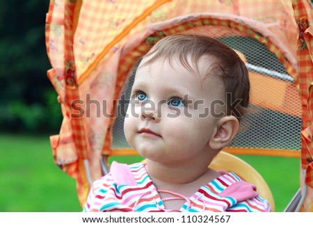 Happy baby face portrait sitting in stroller with nice look outdoor on green summer background