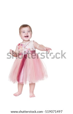 Happy baby girl isolated on white background. child 1 year. Smiling girl standing at full height.