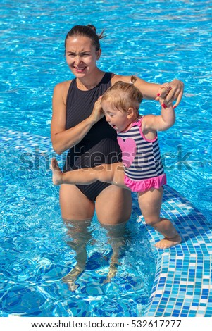 Happy baby girl learn to swim in pool  with her mother on a hot summer day during vacation
