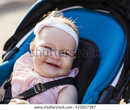 Happy baby girl sitting in a stroller looking at the camera with a big smile