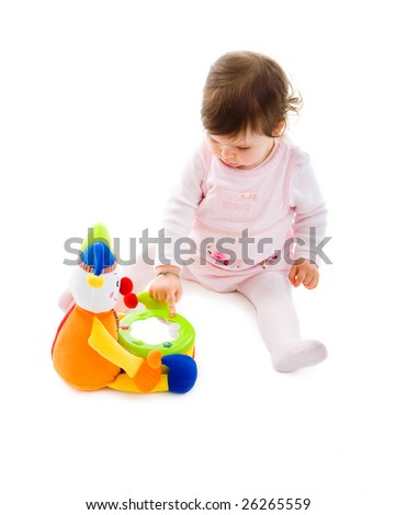 Happy baby girl sitting on floor playing with toy smiling, isolated on white background.