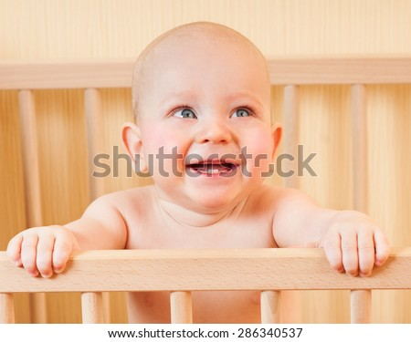 Happy baby in her crib. Smiling baby.