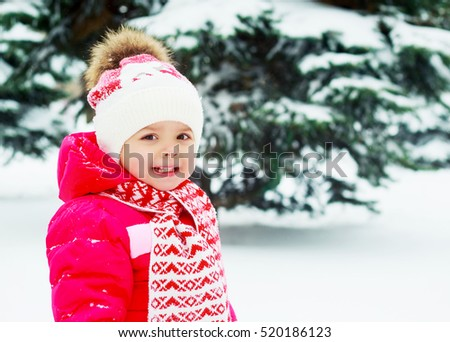 happy baby in the winter park with snow and fir trees