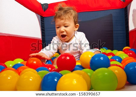 Happy baby playing with balls in playpen