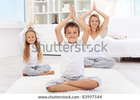 Happy balanced life - woman and kids doing yoga exercise at home - focus on boy