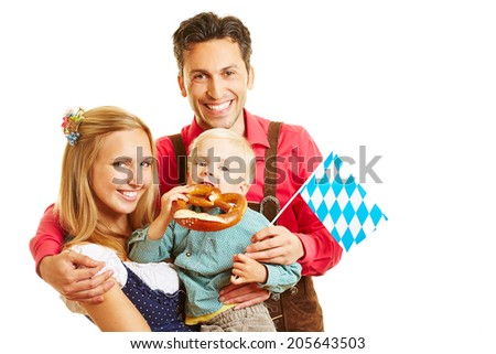 Happy bavarian family smiling with pretzel and flag