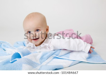 happy beautiful baby on a blue towel