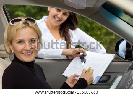 Happy beautiful blond woman signing for the purchase her new car with the smiling saleslady holding the contract through the open window