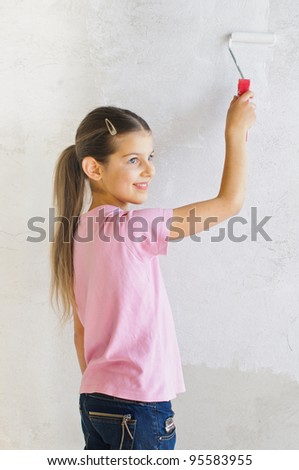 Happy beautiful girl painting a wall with roller