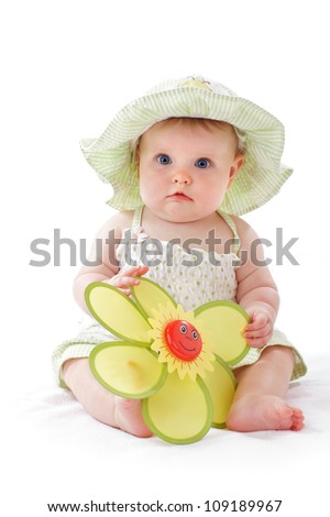 Happy beautiful 6 month old baby girl in green seersucker sun hat and sun dress sits and plays with a big yellow toy daisy. Pastels, isolated on white background, vertical, copy space.