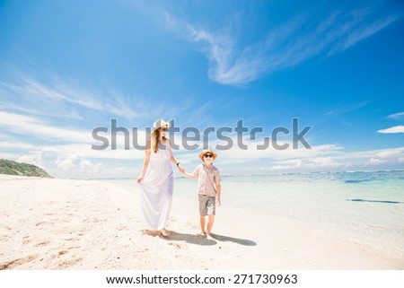 Happy beautiful mother and son walking along the beach in a sunny day with deep blue sky over the ocean on background