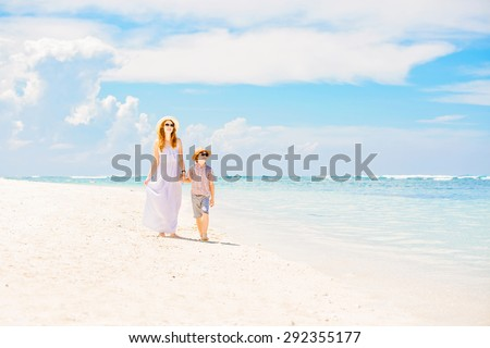 Happy beautiful mother in long white dress enjoying holidays on the beach with her young son wearing hat and sunglasses