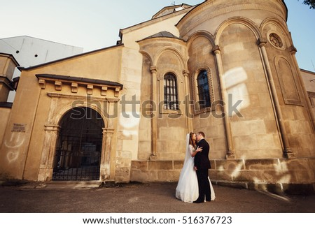 Happy beautiful newlyweds posing in the old city