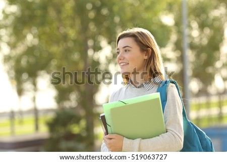 Happy beautiful student girl holding folders and books walking outdoors at sunset