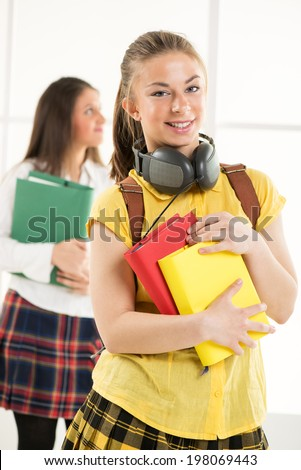 Happy beautiful teenage girl with Colorful books and school bag
